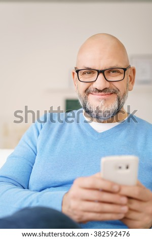 Waist Up Portrait of Casually Dressed Mature Man with Facial Hair Wearing Eyeglasses and Casual Blue Shirt Smiling at Camera and Holding Cell Phone and Relaxing at Home - stock photo