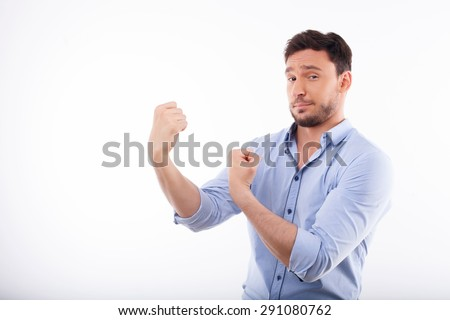 Waist up portrait of cheerful man making his hands in fists and stretching it aside. He is confident and boastful.  Isolated on a white background and there is copy space in the left side - stock photo
