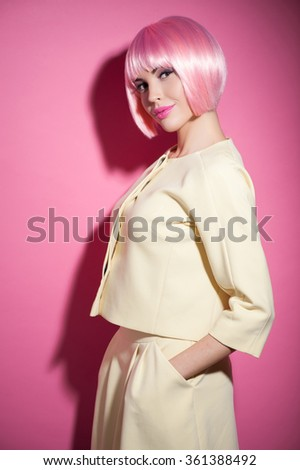 Waist up portrait of cheerful young woman making experiments with her appearance. She is standing and wearing pink wig. The girl is looking at camera and flirting. Isolated - stock photo