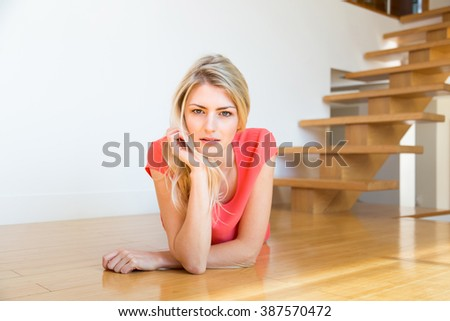 Waist Up Portrait of Confident Young Blond Woman with Long Hair Lying on Wooden Floor on Stomach with Hand on Chin, Smiling and Looking Happy at Home - stock photo