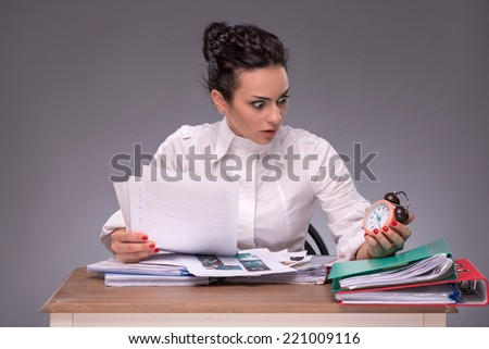 Waist-up portrait of confused girl sitting at the table with a pile of documents and looking with a fright at a clock, isolated on grey background with copy place, concept of time management at work - stock photo
