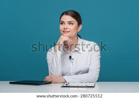 Waist up portrait of elegant woman reporter with Caucasian appearance, who is smiling and dreaming about something while sitting at the table and propping up her head with her right hand. - stock photo