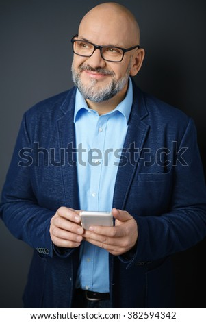 Waist Up Portrait of Fashionable Mature Man Wearing Denim Jacket and Eyeglasses Smiling Confidently to the Side While Holding Cell Phone in Studio with Dark Gray Background - stock photo