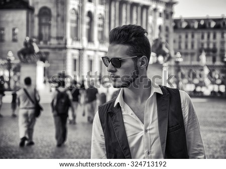 Waist Up Portrait of Fashionable Young Man Wearing Sunglasses and Standing Outdoors in Historical City Square and Gazing with Serious Expression to the Side