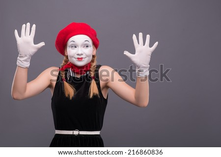Waist-up portrait of female mime with red hat and white face pretty smiling and looking aside and showing her hands isolated on grey background with copy place - stock photo