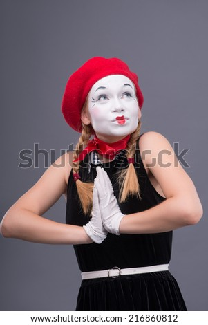 Waist-up portrait of female mime with red hat and white face pretty smiling and looking aside while holding her hands together isolated on grey background with copy place - stock photo