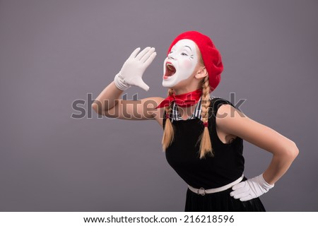 Waist-up portrait of funny female mime in red head and with white face very loudly shouting and looking aside isolated on grey background with copy place - stock photo