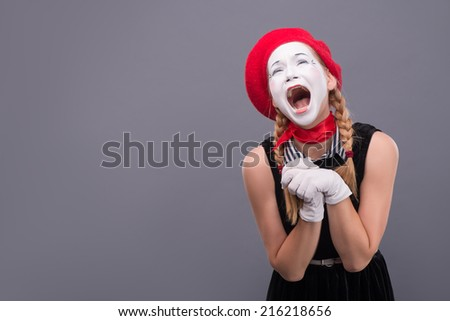 Waist-up portrait of funny female mime in red head and with white face very loudly shouting with closed eyes isolated on grey background with copy place - stock photo