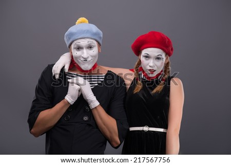 Waist-up portrait of funny mime couple looking at the camera, male mime holding his hands on the chest, female mime hugging him isolated on grey background with copy place - stock photo