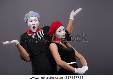 Waist-up portrait of funny mime couple, male mime breeding his hands and confused looking at his girlfriend, who is calmly looking at the camera isolated on grey background with copy place - stock photo