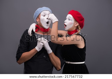 Waist-up portrait of funny mime couple, male mime holding his hands on the chest, female mime touching his nose isolated on grey background with copy place - stock photo