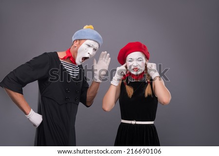 Waist-up portrait of funny mime couple with white faces, male mime shouting on female mime closing her ears with her fingers isolated on grey background with copy place - stock photo