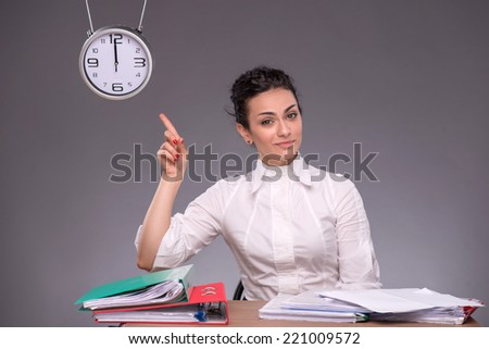 Waist-up portrait of girl sitting at the table in office with a pile of documents and smart showing with her finger at the time on the clock isolated on grey background with copy place - stock photo