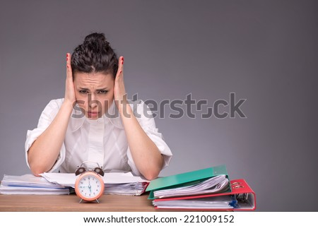 Waist-up portrait of girl sitting at the table with a pile of documents and an alarm clock, holding her head because of headache and upset looking at you, isolated on grey background with copy place - stock photo