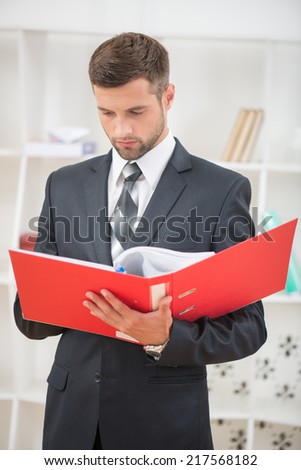 Waist-up portrait of handsome confident businessman standing in office with a red folder in his hands and reading with serious face - stock photo