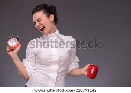Waist- up portrait of happy girl holding an alarm clock and a red cup in her hand with closed eyes isolated on grey background with copy place concept of time management and coffee-break - stock photo