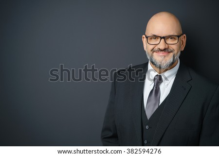 Waist Up Portrait of Mature Businessman with Facial Hair Wearing Suit and Eyeglasses Smiling Confidently at Camera and Standing in Studio with Dark Gray Background with Copy Space - stock photo