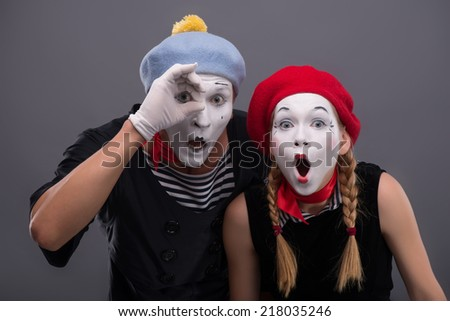 Waist-up portrait of mime couple isolated on grey background with copy place, female mime looking at the camera with a wonder and male mime confused looking at the spyglass  - stock photo