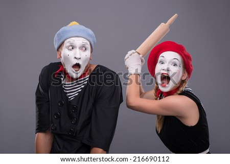 Waist-up portrait of mime couple with white faces, female mime wanting to beat confused male mime with rolling pin isolated on grey background with copy place - stock photo