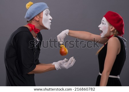 Waist-up portrait of mime couple with white faces looking at each other, female mime giving a yellow pear to male mime giving her kiss isolated on grey background - stock photo