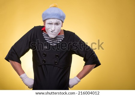 Waist-up portrait of pert mime with white face,  grey hat and red scarf playfully looking at the camera holding his hands on his hips isolated on yellow background - stock photo