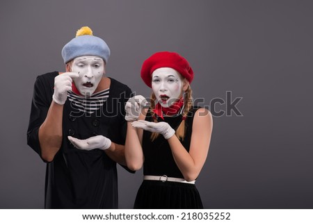 Waist-up portrait of sad mime couple pitifully crying and looking at the camera, both mimes putting their tears in their hands isolated on grey background with copy place - stock photo