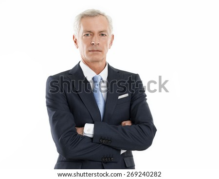 Waist up portrait of senior executive businessman looking at camera while standing against white background.