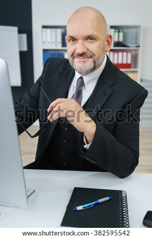 Waist Up Portrait of Smiling Mature Businessman Wearing Suit and Holding Eyeglasses While Sitting at Computer Desk with Notebook and Pen in Modern Workplace Office