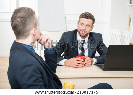Waist-up portrait of two handsome businessmen in suits having a coffee-break in office sitting at the table, with selective focus on one smiling businessman and another sitting back to the camera