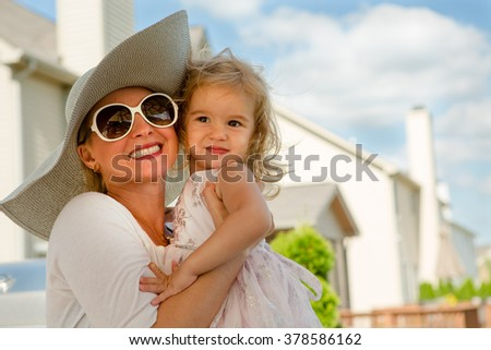 Waist Up Portrait of Woman Wearing Sun Hat and Sunglasses Hugging Young Blond Girl Outdoors in Backyard on Sunny Summer Day
