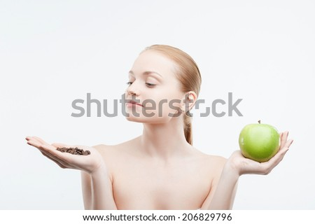 Waist up portrait of young attractive woman in white towel holding coffee beans and green apple in hands, isolated on white - stock photo