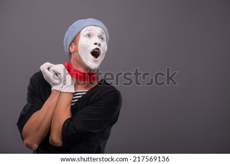 Waist-up Portrait of young male mime holding hands near his face like a girl and playfully looking aside and singing isolated on grey background with copy place - stock photo