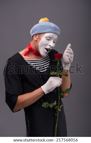 Waist-up portrait of young male mime with white face and grey hat holding a red rose and looking at this flower with tenderness isolated on grey background with copy place - stock photo