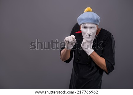 Waist-up Portrait of young male mime with white face, grey hat insidiously scheming something and looking at the camera isolated on grey background with copy place - stock photo