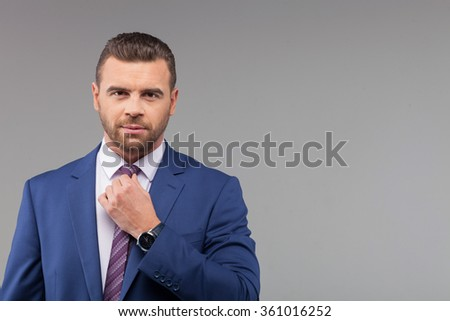 Waist up portrait of young man ready for meeting with business partners. He is standing in suit and adjusting tie. The man is looking forward with seriousness. Isolated and copy space in right side - stock photo