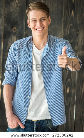 Waist up. Smilling young handsome man looking at camera and showing thumb up. - stock photo