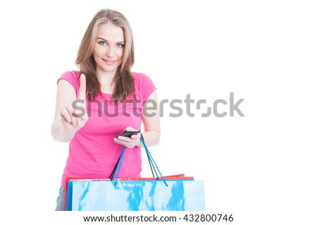 Wait a minute concept with happy shopaholic working on cellphone and holding paper bags with text area isolated on white - stock photo