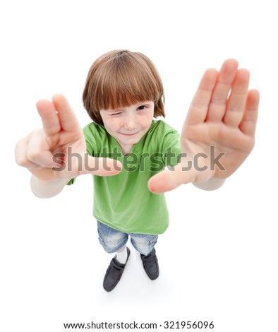 Wait there - freckled young boy looking at you framing with his hands - stock photo