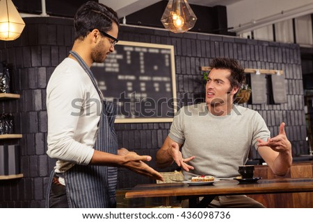 Waiter and customer having a discussion in a coffee shop - stock photo