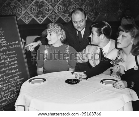 Waiter and customers in restaurant - stock photo
