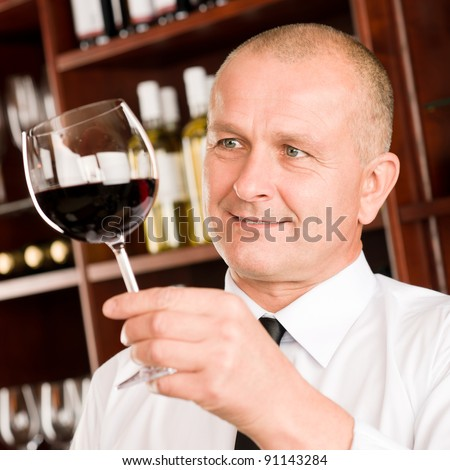 Waiter at bar hold glass of red wine in restaurant - stock photo