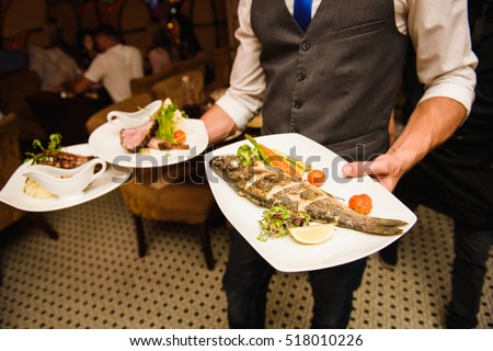 Waiter carries dishes with fish