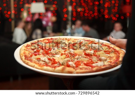 Waiter carrying plate with pizza