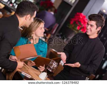 Waiter explaining the menu to a couple at the restaurant - stock photo