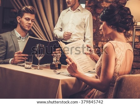 Waiter explaining the menu to stylish wealthy couple in restaurant. - stock photo