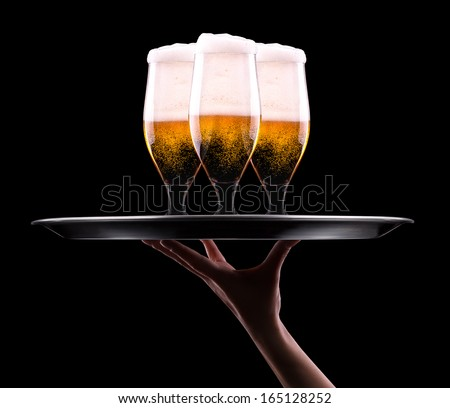 waiter hand and tray with Beer into glass on a black - stock photo