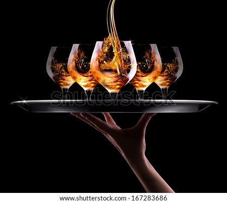 waiter hand and tray with Cognac or brandy on a  black background - stock photo