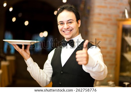 Waiter holding a plate - stock photo