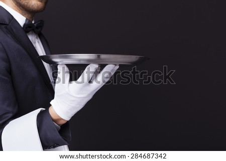 Waiter holding an empty silver tray against dark background - stock photo
