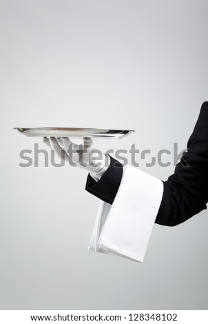 Waiter holding empty silver tray over gray background - stock photo